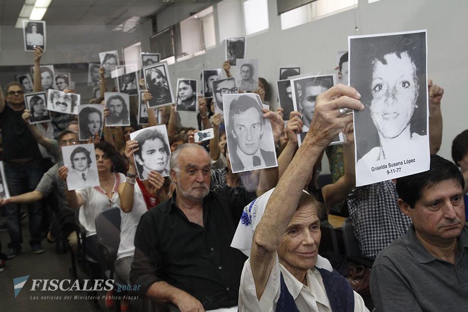 El público levanta las fotos de las víctimas en el final del alegato de la Fiscalía. Fue el 9 de diciembre de 2015.  - Foto de archivo: Matías Pellón/ Ministerio Público Fiscal/www.fiscales.gob.ar